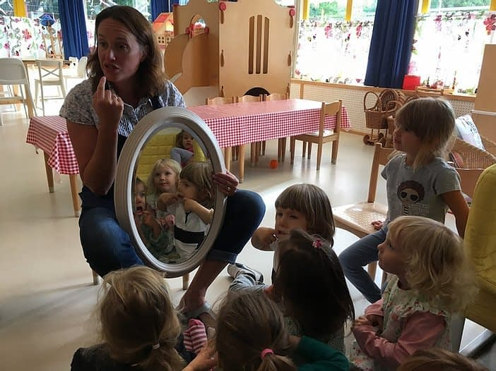 Becky showing a mirror to children - Little Europe International Childcare